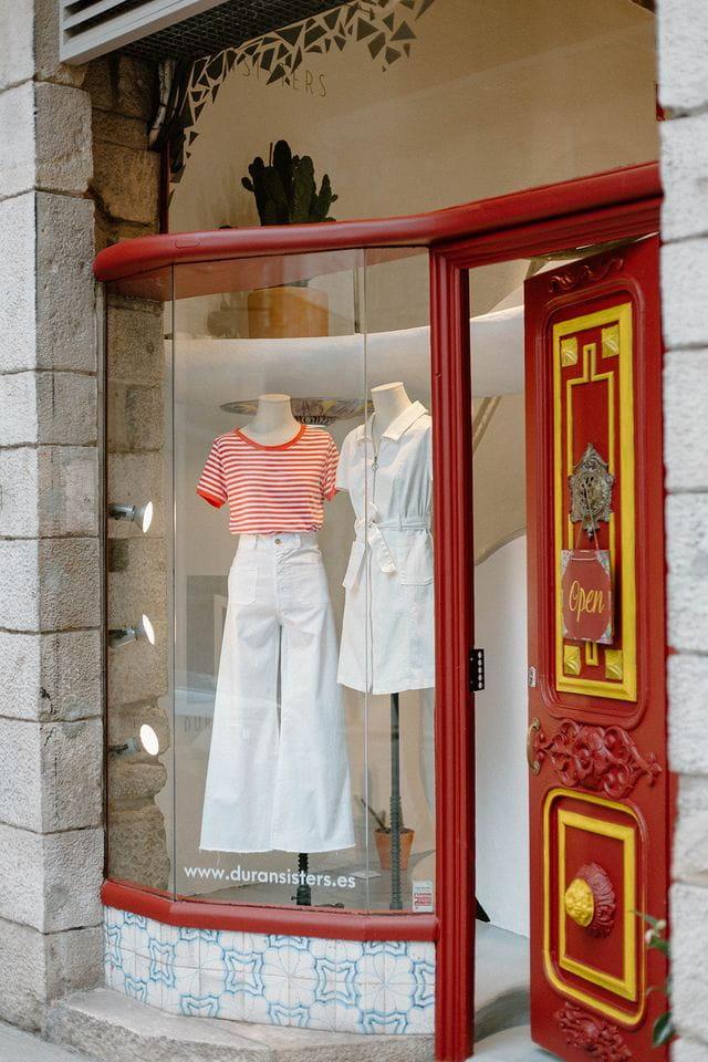 Foto de nuestro escaparate. Con pantalón culotte blanco y camiseta de rayas, y vestido camisero blanco.