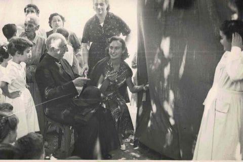 Entrega de diplomes al pati de l'escola per part de l'arxipestre Pere Rifé i Ausió i la directora de l'escola Carmen López Torrejón. Any 1951